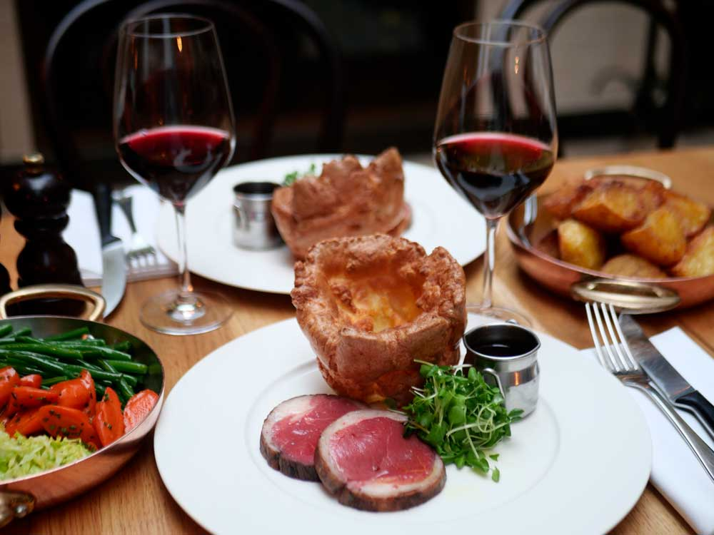 beef and yorkshire pudding and glasses of red wine